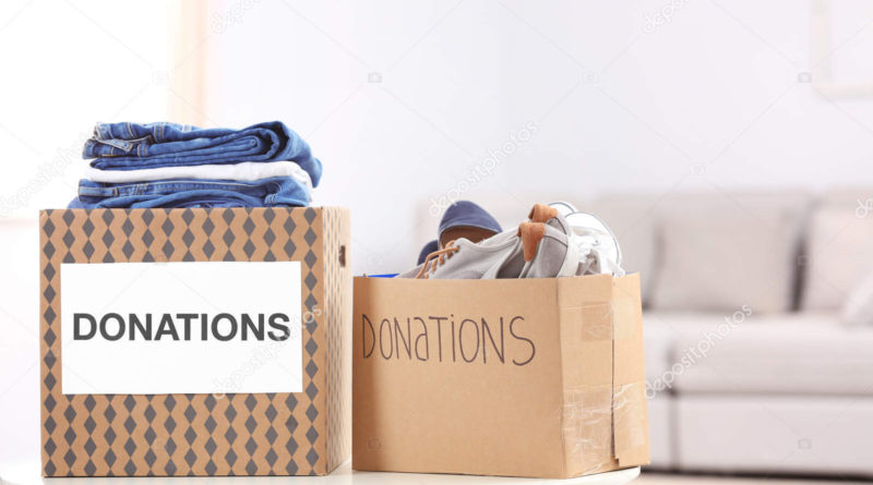 Donation boxes with clothes and shoes on table indoors